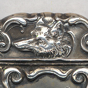 "Rectangular, with curves and counter-curves along ornate perimeter, featuring raised decoration of female equestrian on horse, jumping over wooden fence, tree and grass in foreground and background, scene is framed by elaborate scroll work, lid features fox head with scroll work surround; reverse features variation on decorative scroll work frame, scroll work on lid as well, reserve empty except for incised initials ""J.C.L."" Lid hinged on side. Striker on bottom."