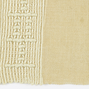 Peach-colored rectangular mat with end borders in a linear design using heavier cord.