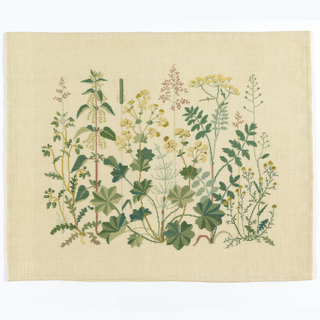 Woven linen pillow with wool embroidery showing group of various wild plants.