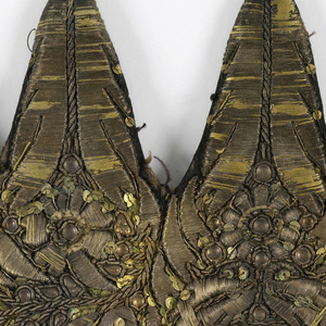 A/ Flat headpiece with rounded top and base with five prongs. Black silk satin densely embroidered with sequins and metallic yarns in symmetrical design of flowers and leaves. B/ Second cap-piece of the same fabrication. Made to be fastened to the top and back of the head.