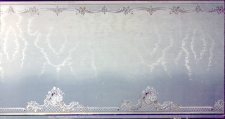 Background of moire pattern, shading from light blue at top to medium blue at bottom. Band of scroll motifs at top edge. Larger scroll and shell motifs with lattice along bottom edge.