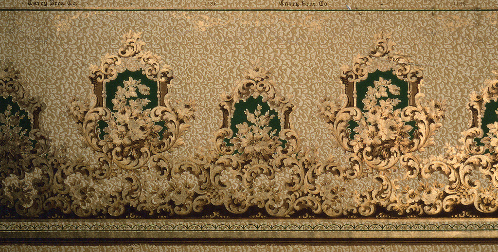 """Alternating medallions framed by acanthus leafs and filled with floral bouquets. Large """"C"""" scrolls and groups of flowers swirl upward towards the medallions from the bottom of the frieze. Background contains a gold, pebble pattern. Printed in gold, beige, and green."""
