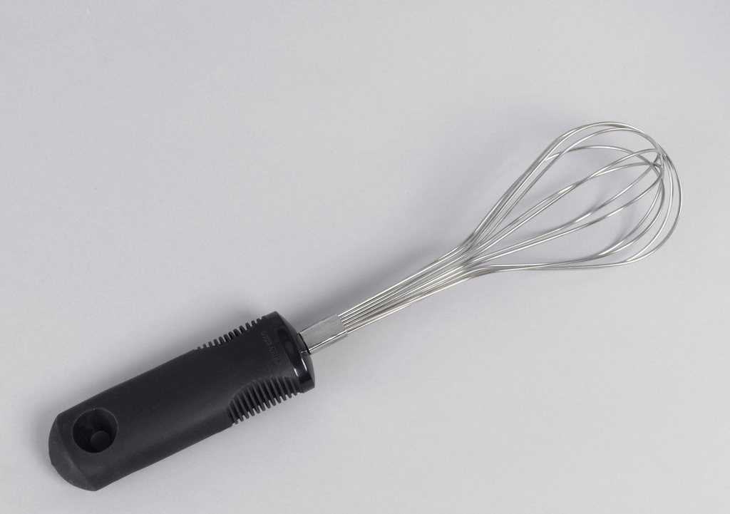 One of a set of kitchen utensils, a stainless steel wisk with a black rubber handle.
