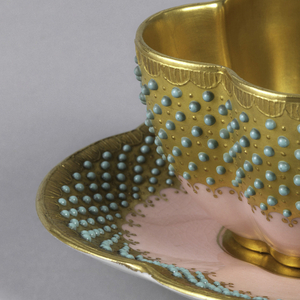 Four-lobed curved demitasse, with double ring handle, and four-lobed saucer. Outisde of cup and inside of saucer decorated with wide gold band with green dots in high reflief, on pink ground. Inside of cup and the handle gilt.