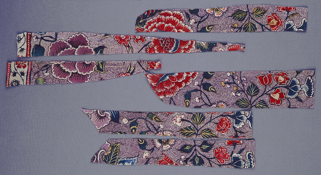 Chintz textile with symmetrical floral pattern in red, blue, green and yellow, with speckled purple background.