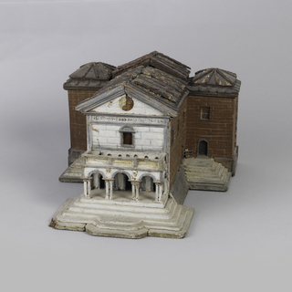 in the form of a Renaissance chapel abutting a brick building behind it, the chapel's front portico of single story, with three arches raised on double columns, surmounted by a single window in the wall, below an open triangular pediment, the back building with three roof tops.
