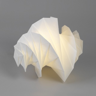 White, horizontally spiraling segmented form containing LED light source on aluminum base with cord.