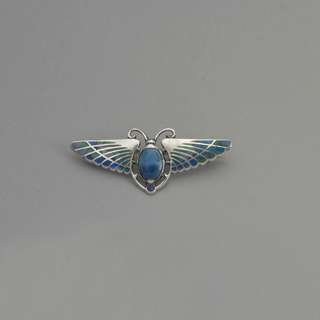 Horizontal brooch in the shape of a scarab with wings spread; the wing are enameled in iridescent blue and green, the central body in blue.