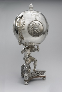 In the form of Atlas supporting the world. Triangular base with openwork decoration, on three ball feet, supports kneeling figure of Atlas holding a spherical urn on his shoulders. Surface of urn with relief decoration featuring four wreathed circular medalions, each suspended from a bow and showing one of four allegorical figures of the continents (Europe, Asia, America, and Africa) with attributes. Two pendant tassels (one concealing a spout) below embossed acanthus leaves supporing two ring handles. Slightly domed cover with moveable laurel-shaped knop in center.