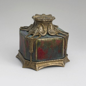 Of square section with canted corners, the mottled green-red glazed stoneware set on a gilt-bronze base, with gilt-bronze scrolling overlay rising to a mount at the lip wth hinged lid.