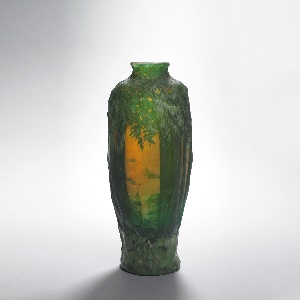 Dark green and orange on an opaque ground, decorated with a high relief forest scene of thick trees with a spire and town roofs in the distance, beneath a bright orange sky; the vase widens as it rises until reaching a narrow neck just below the mouth.