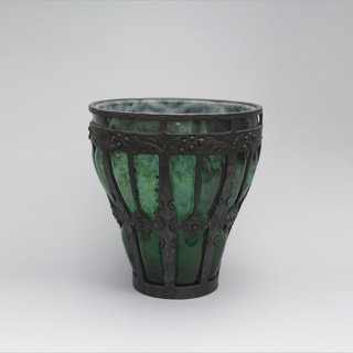 Large, wide-mouthed green vase with metallic inclusions, within a heavy wrought iron framework.