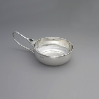 Round dish with a single handle formed by a loop of silver wire, set with a stone.