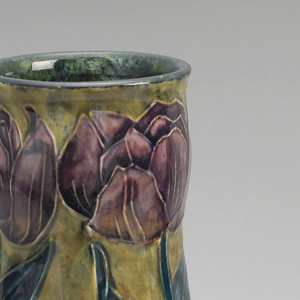 Lead-glazed earthenware with raised slip outline; purple flowers and dark green leaves and stems and a band of small purple flowers over a mustard-colored ground.