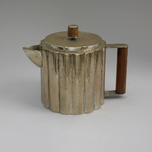 Round body with sharp-beaked spout balanced by a handle running from top to bottom, the handle of walnut connected to the body by thin metal flanges; cylindrical metal fitted cover topped by a finial of walnut between two metal round tabs.