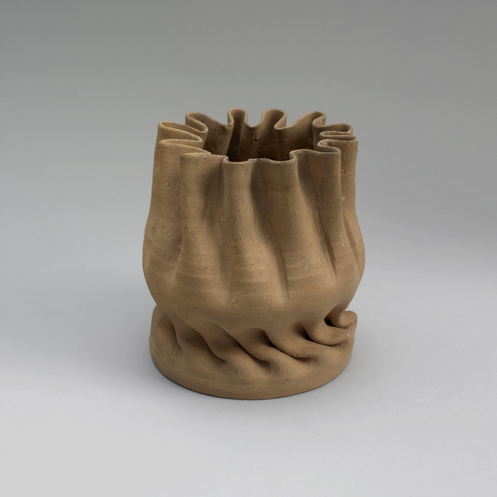 Unglazed/bisque pale red/brown clay, manipulated cylindrical form, very thin walls pinched to create a crimped floriform rim, rising from a folded base then twisted just above the base for about an inch then smooth for less than an inch before the higher folds.