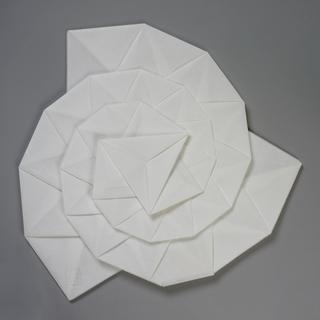 Flattened segmented spiral form.