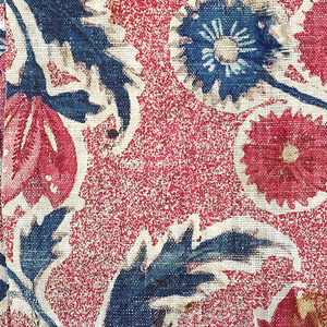 Large, exotic flowers and curving stems in reds and blues on a red speckled background.