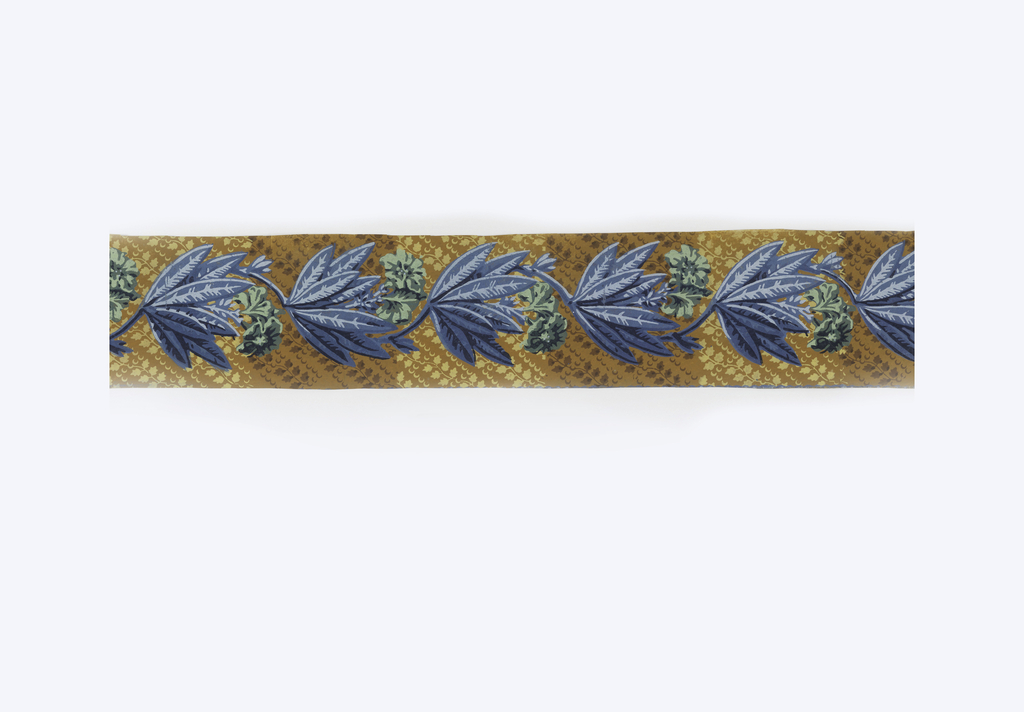Border cut from a strip of wallpaper containing several of these stripes. Design consists of a repeating cluster of long pointed blue leaves with two green flowers. These clusters are placed at regular intervals on a curving serpentine stem. Running in parallel diagonal lines across medium brown field are rows of alternating maiden-hair fern leaves and tiny crescents divided in vertical sections of alternating pale and dark brown coloring.