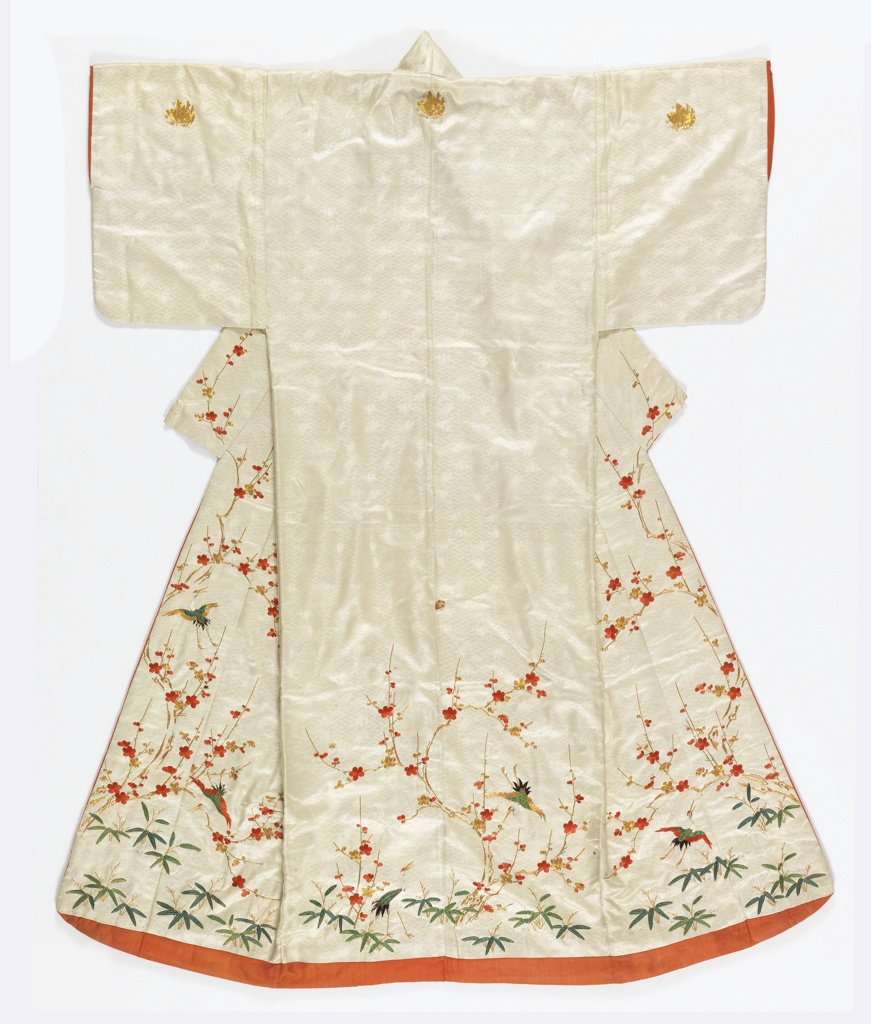 Woman's kimono of white silk satin with woven design of tiny lozenges, tortoises and phoenixes. Embroidered with silk threads in red, gold and green with cherry blossoms, pine branches, bamboo, phoenix and butterflies. Lined with red silk.