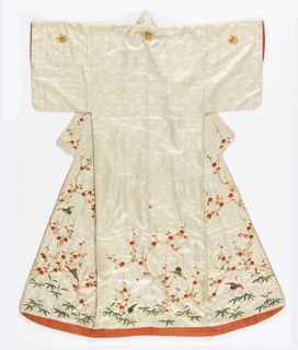 Woman's kimono of white satin with woven design of tiny lozenges, tortoises and phoenixes. Embroidered with silk threads in red, gold and green with cherry blossoms, pine branches, bamboo, phoenix and butterflies. Lined with red silk.
