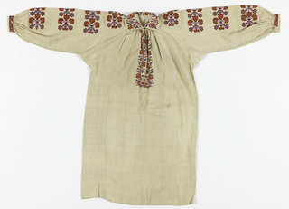 Free-hanging long blouse of fine white linen with raglan sleeves, underarm gussets, narrow open work strip marking each dropped shoulder, deep slit in front of neck, gathered all around neck to turn-over collar. Stylized floral design embroidered in bright red and purple chain stitch on collar, cuffs, around front slit, and on shoulder and down sleeves. Component B is an orange belt in warp-surface cotton cloth with warp fringe and green, blue and white pencil stripes.