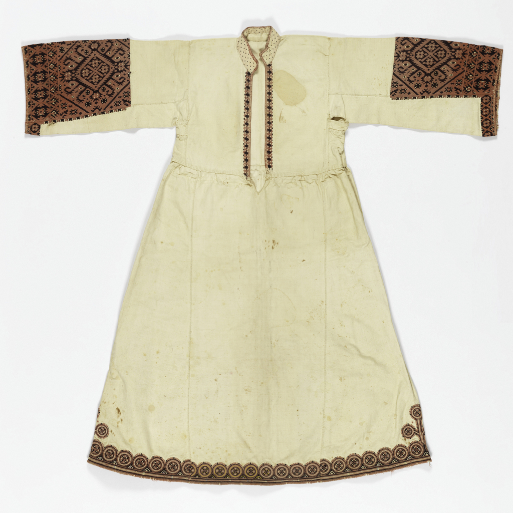 Woman's dress of heavy white cotton embroidered with wool at sleeve, front opening and hem, in rose and dark brownish-red. Highly stylized plant forms in square frame with hook-shaped extensions. Dress opens down front to waist, with standing collar, straight sleeve with square set into arms. Skirt is crudely set on waistline, and shows signs of alteration; it is made in six panels and flares at bottom. Embroidery is mostly in deep rose and black. At the back, two panels of embroidery similar in design to sleeve ornament rise from hem about 11 inches.