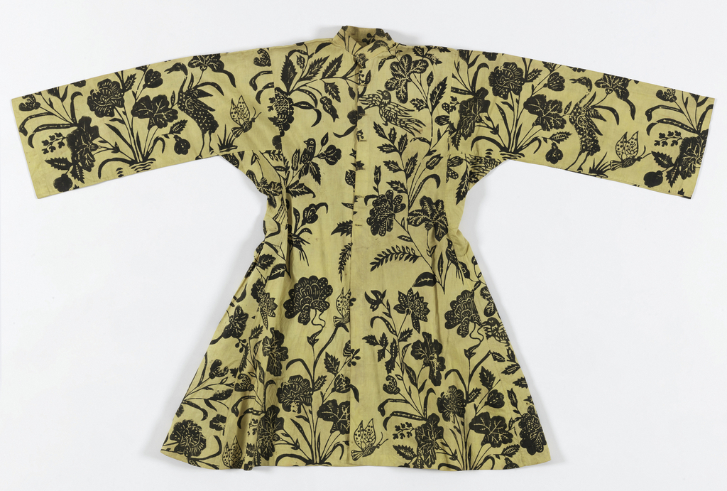 Yellow-buff cotton printed in black with a large bold pattern of exotic floral sprays, birds and butterflies. All  stitching by hand, except for the standup collar, which is stiffened by rows of machine stitching. Cut as a high-waisted, full skirted tunic, probably for a man.