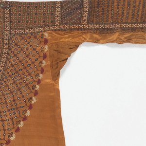 Silk satin dress embroidered with silk thread and small pieces of mica. This dress, called an aba or abo, was made and worn by a Muslim woman in Banni, a remote part of the Kutch district of Gujarat state in western India. The dress has an embroidered pattern over the front, done in incredibly fine chain-stitch and button-hole stitch, with tiny pieces of mirror-glass interspersed regularly throughout the design. The sleeves also use an intricate interlacing stitch called 'bavaliya' or 'hurmitch' in Kutch and Sindh, where it is used in local domestic embroideries. When the dress wears out, the embroidered area can be cut off and re-applied to a new dress. The dress would be worn with matching loose trousers, often with similarly decorated cuffs.