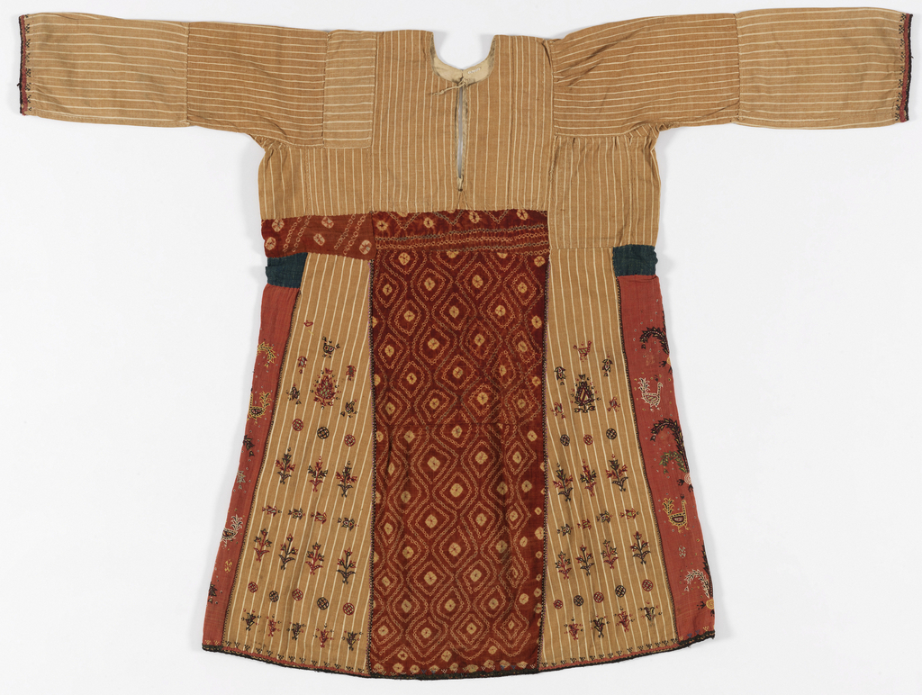 Long-sleeved tunic in handwoven fabric of light brown and white stripes, with inserted sections of tie-dye and embroidery. Round neck, long straight sleeves, pieced. Front and back panels of red tie-dye. Side panels of bright red cotton embroidered with patterns of confronted birds. Side section of embroidered birds, trees, plants; fish in horizontal arrangement.