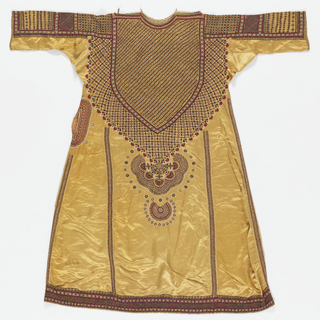 Yellow silk satin dress embroidered with silk thread and mirrors. This dress, called an aba or abo, was made and worn by a Muslim woman in Banni, a remote part of the Kutch district of Gujarat state in western India. The dress has an embroidered pattern over the front, done in incredibly fine chain-stitch and button-hole stitch, with tiny pieces of mirror-glass interspersed regularly throughout the design. The sleeves also use an intricate interlacing stitch called 'bavaliya' or 'hurmitch' in Kutch and Sindh, where it is used in local domestic embroideries. This dress would have been worn with embroidered silk satin trousers (salwar).  Open pocket on right side of dress.