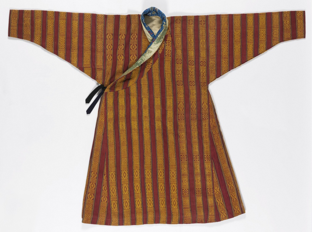 Hand-woven red wild silk robe with vertical stripes of supplementary warp patterning of small geometric motifs in golden yellow, banded by narrow stripes of blue, yellow, and green. Neck bands made of two Chinese brocaded silks, one blue with flowers and the other gold with dragons. Lined with heavy off-white twill. Black tie at side.