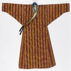 Hand-woven red wild silk robe with vertical stripes of supplementary warp patterning of small geometric motifs in golden yellow, banded by narrow stripes of blue, yellow, and green. Neck bands made of two Chinese brocaded silks, one blue with flowers and the other gold with dragons. Lined with heavy off-white twill. Black tie at side. The robe is gored to produce fullness, with a standing collar and asymmetrical closure. The set-in sleeves are very wide at the shoulder and taper sharply to the wrist, which is worn turned back. The robe is worn looped up at waist and gathered tightly at back, which produces a pouch-like area, at front.
