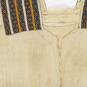 Natural linen dress with beaded straps showing yellow and white herringbone stripes. Skirt with two embroidered panels in yellow, black and red. Border of clover embroidery.