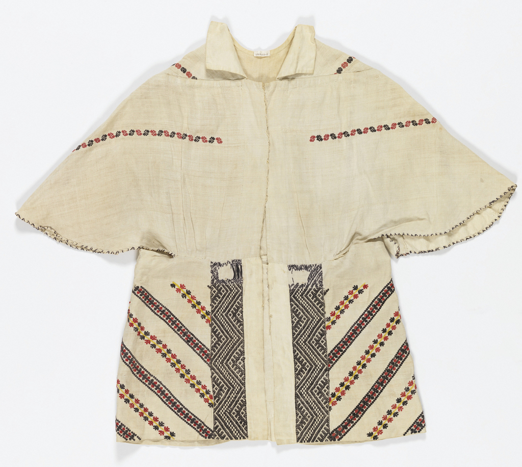 Natural linen jacket with collar. Embroidered horizontal line of black and red S-shaped motifs at shoulders and chest. At bottom, two thick vertical bands of graphic black and white embroidery. Embroidered diagonal lines at either side in red, black and yellow.