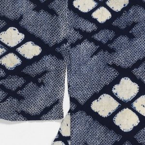 Lightweight summer kimono. Four white petal-like forms inside a deep blue diamond forming a broken lattice. On a closely-tied spotted ground.