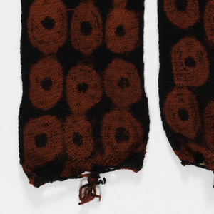 Long, narrow rectangle of wool sprang, tie-dyed with large red rings on a black ground.