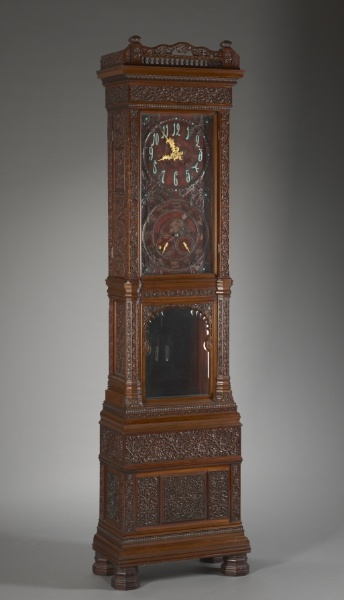 heavily carved with scrolls and stylized floral motifs surrounding two glazed compartments, the upper with clock face with Arabic numerals, and a lower dial, the lower with opening for pendula, with pierced carved crest rail.