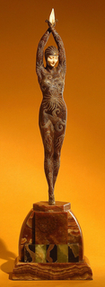 Female dancing figure standing on demi-toe, hands together above head, costumed in reptile texture, brown, with gold decoration covering figure completely, except face and hands which are ivory and are finely chiseled.  Base of onyx pieces of various colors, mostly brown/beige, in various geometric shapes.
