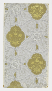Drop-repeating gold quatrefoils centered with formalized gold foil flowers and leaves. The spaces between are embellished with foliate arabesques and flower medallions, all the elements being connected by beaded strapwork in grisaille.