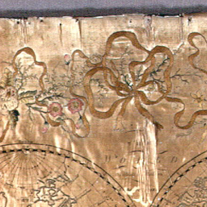 """Embroidery on top of printed satin foundation of two globes of the world.  Printing on satin reads: """"The World with all modern boundaries.""""  Elaborate border of embroidered flowers and ribbons."""
