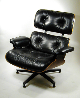 Lounge chair composed of three molded plywood shells, covered on their upper sides with leather-upholstered cushioning.  The armrests are also padded with foam and covered in leather.  The chair and ottoman rest on cast aluminum swivel bases with polished and matte black surfaces; the aluminum back braces are finished in the same way.