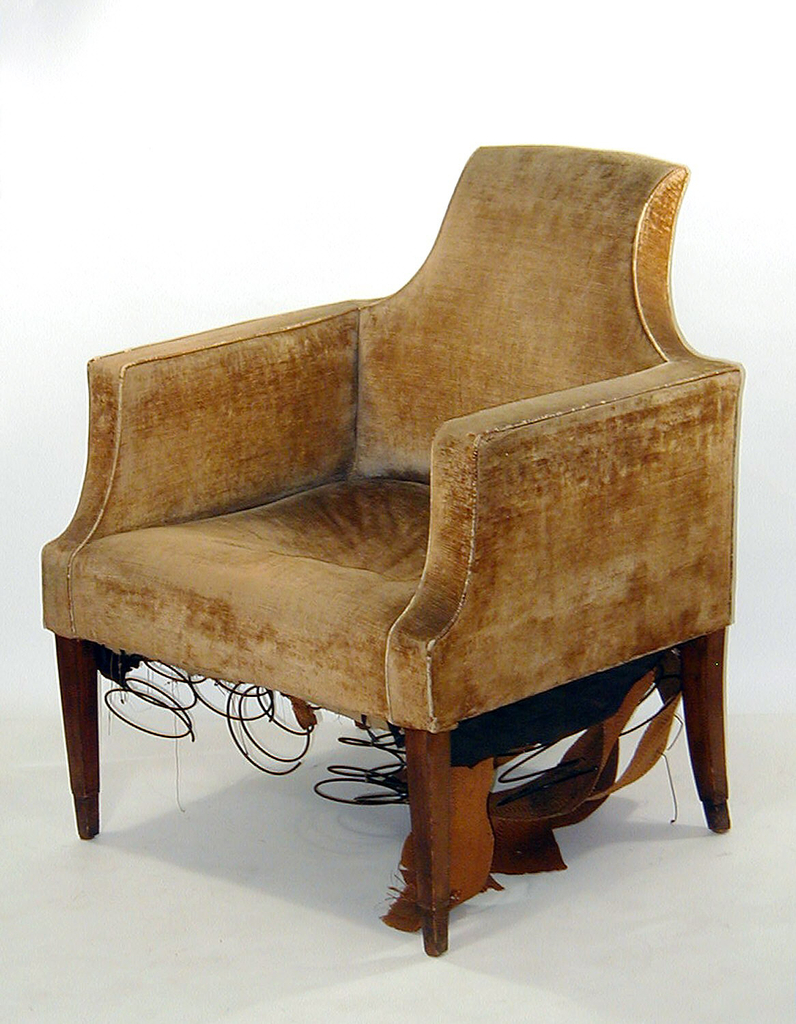 Upholstered armchair with shaped back, finished in a straight line leading down over two symmetrical curvatures in the back's frame.  Similar curvatures lead from each armrest to the chair's seat.  Gold colored velvet upholstery.  Simply cut wooden legs, tapering, and with a carved indentation to indicate chair's feet.