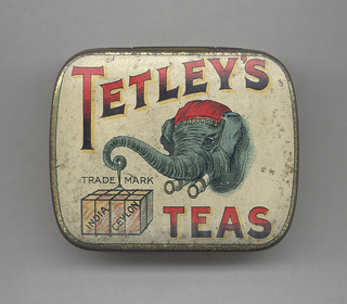 """Rectangular, rounded corners, with transfer printed decoration on lid, inscribed """"Tetley's Teas"""" in large red and black type-face, highlighted in yellow, featuring central image of blue elephant's head with red kerchief, elephant holds at end of curled trunk box on a string, box inscribed """"Indian Ceylon,"""" above box inscription reads """"Trade Mark,"""" all on off-white ground, edges, sides and underside gold. Lid hinged at back. Striker on underside."""