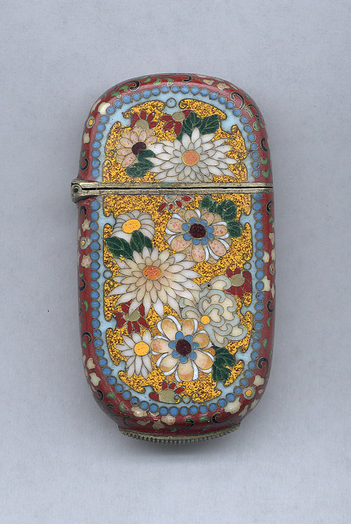 Oblong oval, featuring all-over polychrome, cloisonné, floral decoration, dominant oval reserve displays chrysanthemums and other floral motifs on mottled yellow ground with surround of blue beading, all sides display delicate floral motifs on iron-red ground, reverse features oval reserve with assortment of butterflies on deep green ground, punctuated with specks of metalic copper, and surrround of blue beading. Lid hinged on side. Striker on bottom.