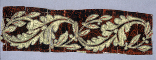 Applique of leaf pattern in gold-faced fabric on previously stamped red velvet.