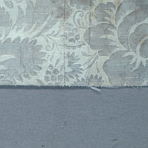 Symmetrical floral pattern in silver and white.