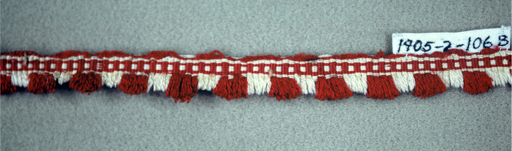 Red and white fringe with a patterned heading and a red and white thread skirt. Red threads are longer than the white.