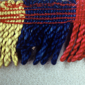 Red, blue and yellow fringe with a soumak heading. Skirt threads are looped and twisted to form stripes.