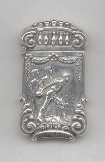 Oblong, curved lid and sides, raised c-scroll motifs at slightly protruding and rounded corners, featuring raised decoration of bowler in mid stride, 2 players behind him, swags and flowers above, background of swirl motifs, lid features smaller reserve of 5 bowling pins in a row. Reverse features empty reserve, c-scrolls, swags, flowers and beading on lid. Lid hinged on side. Striker incorporated into decorative c-scroll on bottom.